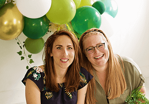 Two colleagues smiling with green balloons.