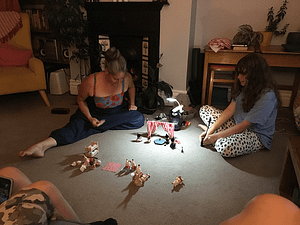 adult and child sat on the floor playing with Sylvanian toys.