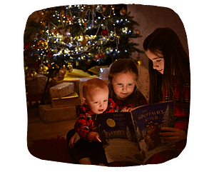 three children reading a book under a Christmas tree.
