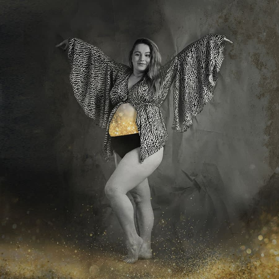Black and white portrait of pregnant woman, fabric flying Pregnant mother posing like a Phoenix. Gold glitter overlaid on her bump. Alternative maternity portrait, Lancaster PhotoBaby studio.