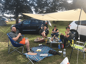 family sat around at a campsite.