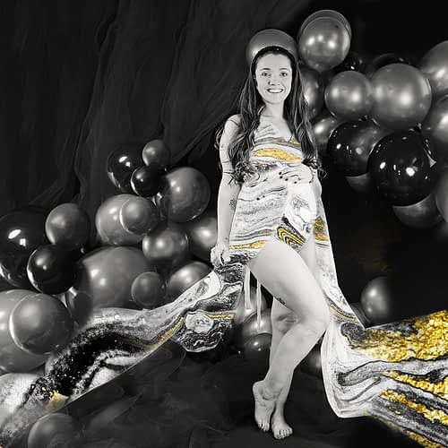 Black and white portrait of pregnant woman, fabric flying behind her like a cape. Gold glitte Alternative maternity portrait, black and white with gold, marble overlay on clothing. Lancaster PhotoBaby studio.