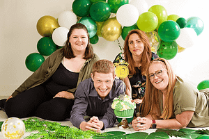 Team photograph with cake and balloons.