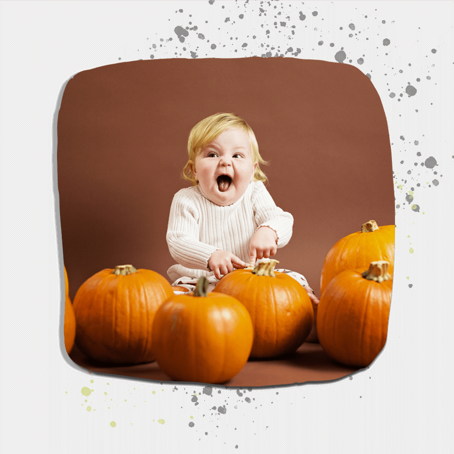 excited toddler sat with pumpkins.