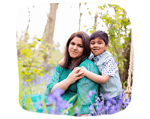 Mother and son cuddling in the bluebell woods.