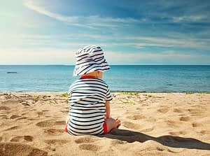Nine month old baby boy sitting on the beach in beautiful summer day.