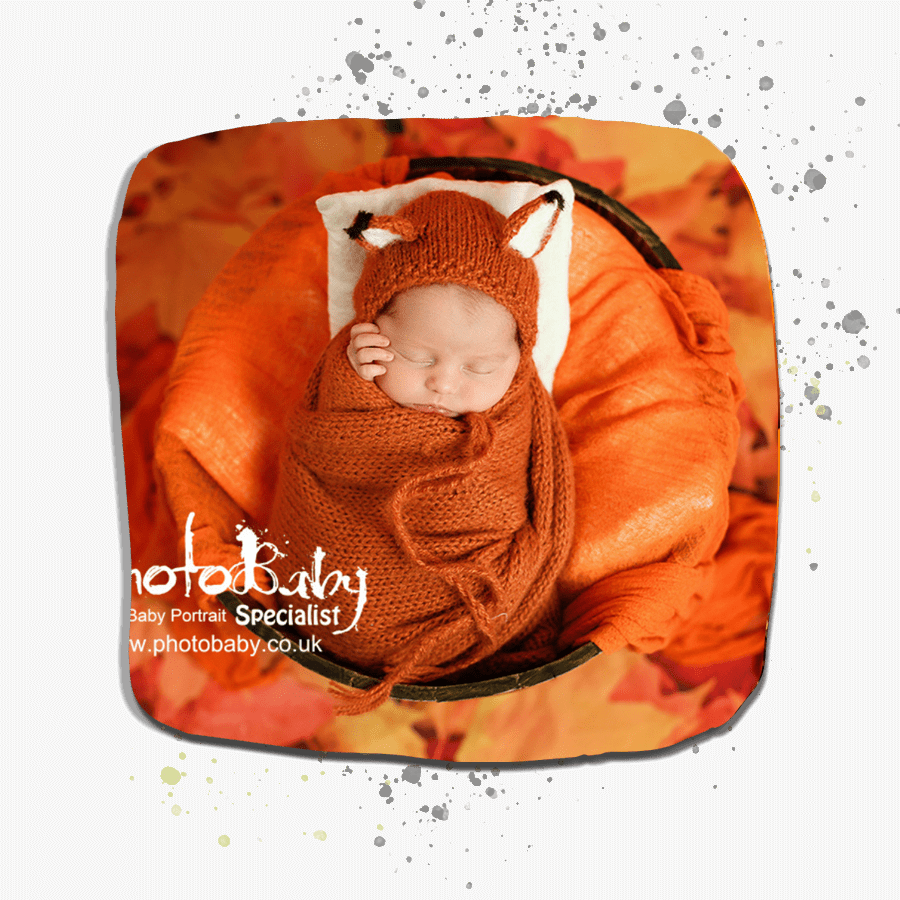 baby in in a barrel with fox hat and orange blanket surrounded by orange leaves.