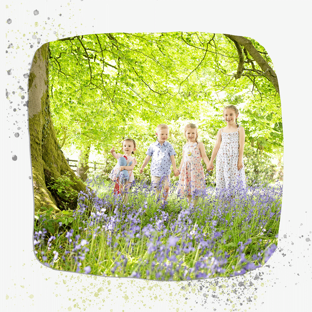 four children holding hands in the bluebells.