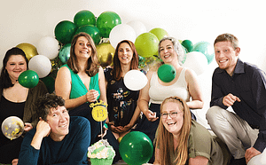 Photograph of PhotoBaby team with green balloons.